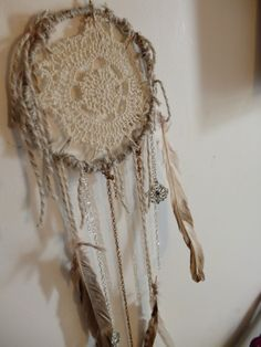 Dreamcatcher I made out of a metal ring, wool, doiley, chain, embellishments and feathers.  Still need to add a few things.  I ordered these little starfish that I will stick on.  I wanted a beach/boho look, so I used neutral colours.