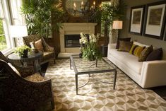 Brown-centric living room design with glass and steel coffee table.  Two ornate armchairs with a small round table face a white sofa.