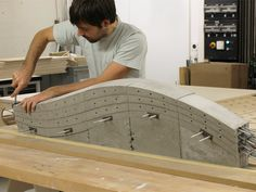 Longitudinal post-tensioning of the components of the 1:10 prototype, with project author Lluis Enrique working on the model. The specific geometry of the components avoids the need for formwork, reduces work on the construction site and minimizes the production of waste.