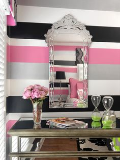 Wide wall stripes in black, white, gray and pink turn a teen girl's bedroom into a flirty, fun space for her to hang out with friends. An Art Deco-style wall mirror and mirrored dresser reflect the space's strong colors and patterns.