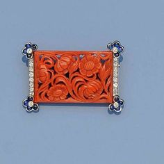 French coral, sapphire and diamond brooch, circa 1920s. The foliate carved rectangular coral panel edged with two vertical lines of brilliant-cut diamonds, each corner with a flowerhead cluster of four cabochon sapphires and diamond centre, French control marks, length 3.7cm.