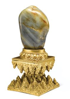 A JADE BOULDER AND AN ORMOLU GILT-BRONZE STAND QING DYNASTY, QIANLONG PERIOD The smoothly polished stone of a greyish-celadon tone with variegated black and russet patches and inclusions, mounted on a beaded lotus base atop a waisted square rockwork plinth in gilt-bronze; sold 2,000,000 HKD; 30/11/17. ||| sotheby's hk0754lot95x7men