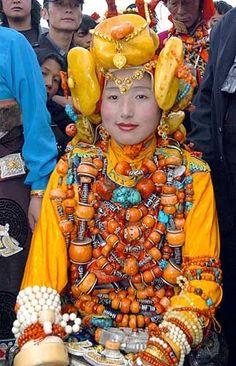 Tibetan costume and jewelry.  huge pieces of amber(yellow) on her headdress. Amazing