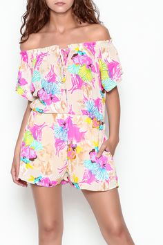 c96f2657039c Off the shoulder tropical print romper with elastic and ruffle trim along  tie front neckline.