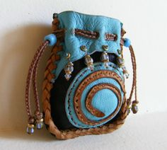 ~~~ POCKET FETISH BAG ~~~    This little guy is soooo cute. Big enough to hold a fetish or crystal and small enough to carry in your pocket.    Made of jet black Navajo Deerskin (from NE Arizona) and sky blue sheepskin. The bag is entirely hand stitched, with saddle colored deerskin in Spanish Edge Lacing, as is the center spiral. Faux sinew has been used for the applique stitching.    Along the top edge of sky blue, 5 little strands hold vintage brass, seed beads, antique Venetian striped…