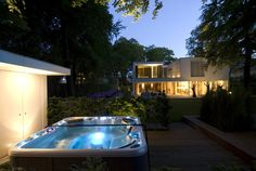 An Exciting Outdoor Hot Tubs With Blue Color Scheme For Modern House With Concrete Flooring And Wooden Garage Door Asymmetrical Modern Architecture in the Netherlands Home design