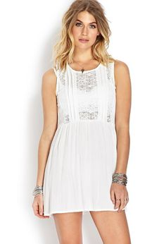A woven dress featuring lace panel inserts and pleated detail. Round neckline. Sleeveless. Unline...