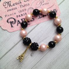 Paris pink & black and goldtone Eiffel Tower charm bracelet. It is a 6.5 inch bracelet on stretchy cord with acrylic pearl like beads, matte finish beads, rhinestone beads and a gold tone Eiffel Tower. The matte finish pink beads are a stand out. Perfect party favors for your Paris themed celebration. If you need adult sizes please message me before purchase. Bracelets are recommended for girls 3 years and up. You are purchasing 8 completely assembled 6.5 inch bracelets - 8 Party Favors ...