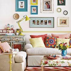 sala decorada no estilo boho chic, bohemiam chic com almofadas de estampas e cores variadas, tapete vermelho com branco, luminária amarel, quadros e porta retratos na parede com molduras coloridas, mesa de centro com estampa floral