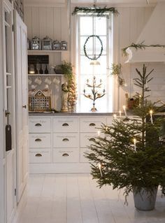 Beautiful kitchen... and I'm thinking about sticking our tree in a bucket this year. Keeps the tree nice and hydrated and it looks a lot better than most Christmas tree stands.