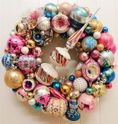 """""""Christmas Carousel"""" is a stunning wreath made with vintage, mid-century ornaments in pink, aqua, gold, silver and white. Its centerpiece is a fantastic, unique large mid-century, mica tree topper from the sixties. Among the ornaments are Shiny Brite; several beautiful, hand painted Polands; West Germans; indents and retro sequin/beaded. It also includes a wonderful vintage, multi-color bell corsage.  All ornaments are previously owned vintage pieces and thus bear the wear of loving use…"""
