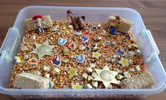 Western Sensory Bin - Cowboy/Cowgirl Sensory Bin - Toy Story Sensory Bin - it contains unpopped popcorn kernels, gold nuggets, western erasers, sheriff badges, red/yellow star confetti, hay bales, and toy story characters (Jessie, Woody, and Bullseye) Preschool Sensory Activity