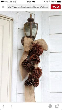 Pinecone and burlap bow fall deco decoration hanging from inside or outside wall lights. Simple. Quick and easy. Use fishing line to tie pine cones together.