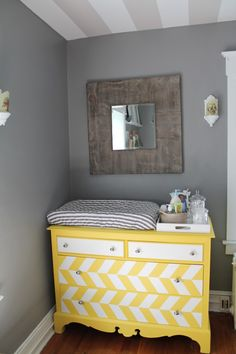 Yellow herringbone dresser + changing table in a yellow and gray nursery. Love this look!