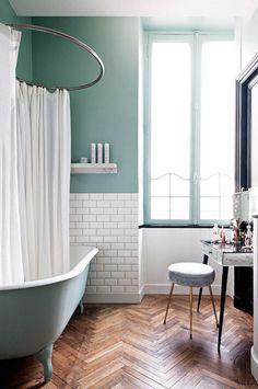 Almond green bathroom with wood herringbone pattern floor, freestanding clawfoot bathtub, huge windows and darling vanity... We want it all!