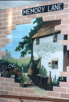 Memory Lane mural painted in a care home, showing a brick wall with a hole through it, through which a farm house and a country landscape can be seen.