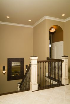 Traditional Staircase with rod iron balusters, dark banister & white post.