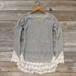 A romantic sweater that is perfect for crisp fall weather. Creamy lace and a chunky heather gray knit pair for the perfect sweater. Beautifully designed, this sweater features a soft cozy knit, ribbed collar, long lace trimmed sleeves, and the sweetest lace ruffle hem. Longer length that can be worn as a tunic or sweater dress with leggings. The perfect sweater to cozy up to this fall.