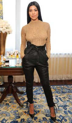 Kourtney Kardashian in a camel sweater and high-waisted paper-bag waist pants