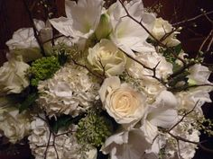 Closeup of arrangement with naked seeded eucalyptus, hydrangeas, cream roses, white amaryllis and flowering branches • Parker Voss for In Bloom New York