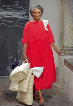 Daniela Gregis, an Italian designer, is shown wearing a very modest day dress. While being a fashion designer, Gregis is an icon for fashion along with her line of clothing. Gregis' dress is very modest but is a vibrant color so it isn't too plain and people will still find interest in it.