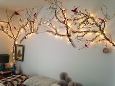 I love this project so much.  It was really simple, my mom and I picked up tree branches after a tree pruning nearby and played around to find the best fits.  We attached the branches to the wall by tying a piece of twine around a screw head and wrapping the twine around the tree branch, so there's only one screw hole per branch.  I wrapped the tree branches with old christmas lights from my folks house and little paper flowers.  Bonus: the lights turn on via clap-light.