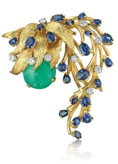 How fabulous is this brooch? A spray of sapphires and diamonds wraps around the central emerald with twining grace. How would you wear it? (Via Phillips.)