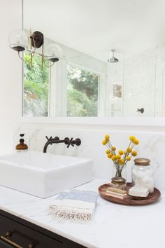 Close-up shot of a white marble counter and backsplash framing a rectangular vessel sink with wall ...