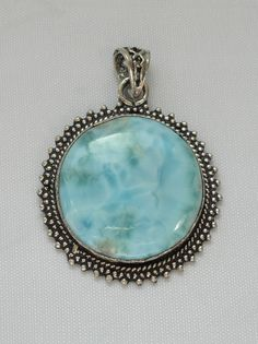 "Stunning hand-scrolled polished cabachon Caribbean Larimar gemstone pendant, bezel-set in 925-hallmarked sterling silver with intricate scrollwork setting and bail. Length: 1.75"" including bail. Width"