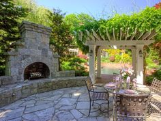 If you want to create an additional entertainment area that adjoins a backyard swimming pool, consider this intimate configuration of a private dining area with a built-in granite fireplace, pavers and a vine-covered pergola entrance by Hoffman Landscapes.