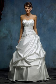 M9809L - Satin A-line wedding dress with sweetheart neckline. Asymmetrical pleated bodice with beautiful bead detailing at the bust and hip. Chapel length train.