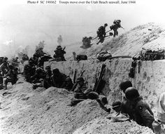 "Photo #: SC 190062 Normandy Invasion, June 1944 U.S. Soldiers of the 8th Infantry Regiment, 4th Infantry Division, move out over the seawall on ""Utah"" Beach, after coming ashore. Other troops are resting behind the concrete wall. Photo dated 9 June 1944, but probably taken on ""D-Day"", 6 June 1944. Photograph from the Army Signal Corps Collection in the U.S. National Archives."