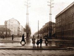 Bambini in posa all'imbocco di viale Umbria, fotografato da piazzale Lodi. A destra si nota l'imponente struttura della TIBB: Tecnomasio Italiano venne fondato nel 1871 a Milano con lo scopo di produrre motori elettrici e generatori di corrente. Nel 1903 il Tecnomasio Italiano venne acquisito dall'azienda svizzera Brown Boveri. Diverrà un'importante produttore di locomotori. Quando nel 1991 venne aperta qui la fermata della linea 3, si volle ricordare nel nome della stazione…