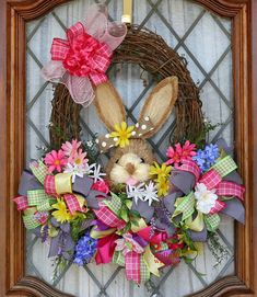 This Spring/Easter wreath with a bunny head will be so festive on your front door. It was made on an oval grapevine wreath base. There are three large bows with an assortment of greenery and silk flowers tucked all around them. Clusters of pink deco mesh sit beneath the bows. A cute