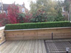 Artificial Boxwood Hedging, made bespoke by Red Hot Plants for a customers own trough. The fake Box Hedge acts as a screen on the decking.