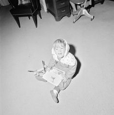 21 Jan 1963. John F. Kennedy, Jr. (holding a photograph of Marine One airborne over the South Lawn) sits on the floor with a toy helicopter in the office of the President's Secretary (Evelyn Lincoln), White House, Washington, D.C.