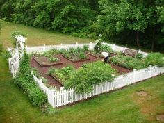 Fenced garden with raised beds. Love the white picket fence and trellis entrance. Beautiful!