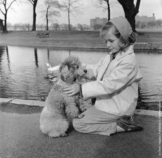 A French poodle and its young owner spend quality time together by a pond in the park. (Photo by Three Lions/Getty Images). Circa 1955