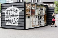 It is shaped like a container, the black staked wooden outside gives the feeling of a barn and the glass windows and the revolving door tell's you its modern. Inside we contrasted the industrial look of the refrigerators with the warmth of wood and the freshness of the little tiled counter.