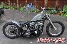 Gray evo softail bobber with short blacked out exhaust and mid-controls