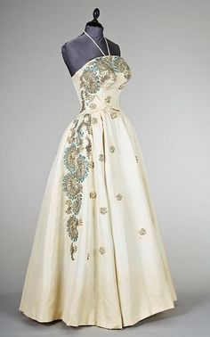 A Pierre Balmain couture ball gown, circa 1953-6, the gown of silver-grey silk faille with strapless bodice and full skirt with lavish Lesage silver and blue embroidery with raisedwork C scrolls studded with pastes, satin rosettes, metallic blue embroidery, simple bow to the front