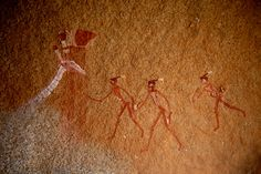 NAMIBIA. Polychrome Bushman/San paintings apparently depicting the head and white neck of a giraffe facing right approached by 3 decorated figures (on right). The paintings are located behind a narrow ledge high up on the Brandberg massif and it is probable that this was ritual site, perhaps a rain making site. #namibia #africanrockart http://africanrockart.org/tara-african-rock-art-photo-gallery/namibia/
