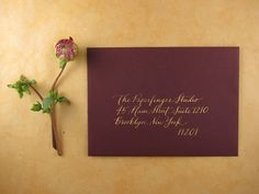 Oxblood envelopes with gold calligraphy from Paperfinger