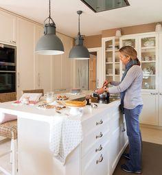 Cocina con mobiliario en blanco e isla. Taburetes de madera y fibras y las lámparas con pantalla metálica deCoton et Bois.
