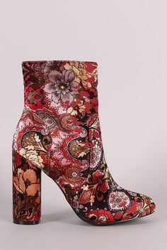 These booties feature a velvet fabrication with a multi colored floral print, wrapped round chunky heel, pieced design with top stitching, single sole, lightly padded insole for comfort, and a side zi
