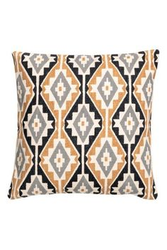 Cushion cover in a cotton weave with a patterned front, solid colour back and concealed zip.