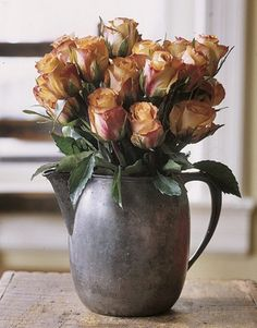 Old pewter pitcher filled with beautiful roses in beautiful contrasting hues!