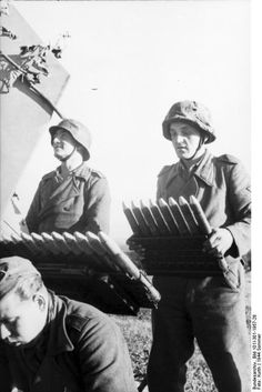 Crew of a German 3.7 cm Flakzwilling 43 anti-aircraft mount feeding its twin guns with 8-round clips, northern France, Jul-Sep 1943.