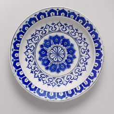 Plate, ca. 1580 Iznik, Turkey Fritware, polychrome painted under a transparent glaze. This sixteenth-century dish in cobalt blue was produced at the famous kilns at Iznik, in western Anatolia. Stylized variations of lotus petals, ultimately of Chinese inspiration patterned into a sunburst of powerful Islamic design, Chinese influences on Islamic art peaked in the thirteenth and fourteenth cent. The Mongol Ilkhans who governed the Near East from their capital at Tabriz,