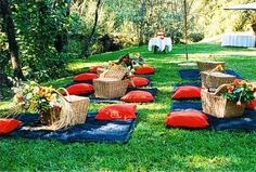 individual baskets of coolers already on blankets. Coolers are filled with red and white wine with a cheese board. Bridesmaids go around and serve sammies with something else in serving trays for everyone to pick.